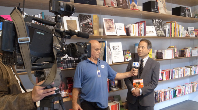 Vice President Masami Kobayashi being interviewed in front of the donated manga books