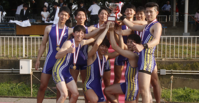 The nine members of the men's eight squad beaming as they hold up the winner's trophy<br/>  (photo by Meidai sport newspapers club)